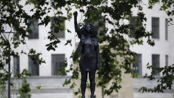 İngiltere'deki ırkçılık karşıtı protestolarda devrilerek nehre atılan köle taciri Edward Colston'un heykelinin yerine, sabahın erken saatlerinde gerçekleştirilen 'gizli bir operasyonla' heykeli deviren protestoculardan birinin heykeli dikildi. - Sputnik Türkiye