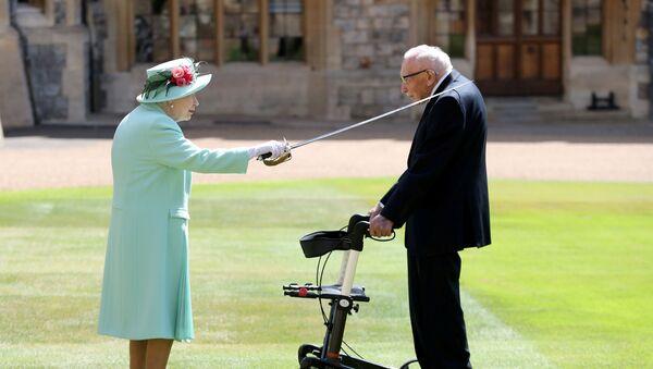 Kraliçe 2. Elizabeth karşısında yürüteçe tutunarak duran Tom Moore'u babası Kral 6.George'un kılıcıyla dokunmak suretiyle şövalye ilan etti. - Sputnik Türkiye