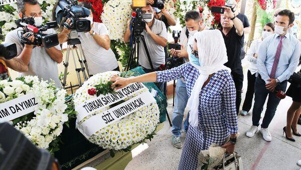 Cenaze törenine katılan şarkıcı Gülben Ergen, Dursunoğlu'nun tabutuna gül bıraktı. - Sputnik Türkiye