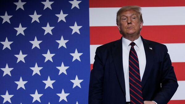 Kızılhaç merkezini ziyaret ederken ABD bayrağı önünde duran Başkan Donald Trump - Sputnik Türkiye