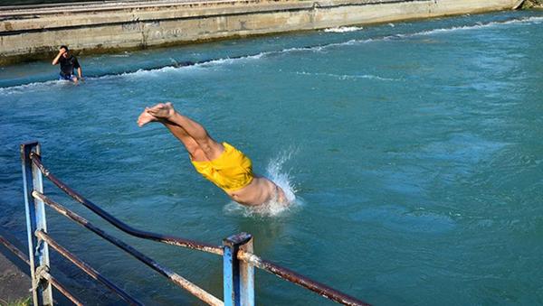 Adana'da gençler, sulama kanallarında yüzmeye devam ediyor - Sputnik Türkiye