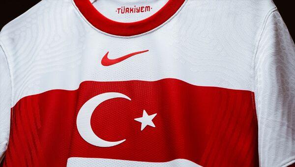 Türkiye A Milli Futbol Takımı'nın Nike tarafından hazırlanan iç saha ve dış saha formalarının tanıtımı yapıldı. Geleneksel renkler ve sembollerden ilham alınarak tasarlanan formalarda bayrak ve bant tasarımın merkezini oluşturuyor. Büyütülmüş ay-yıldız, kırmızı bantın ortasında yer alıyor. - Sputnik Türkiye