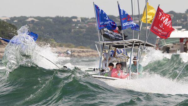 Teksas eyaletinin başkenti Austin kenti yakınlarındaki Travis Gölü'nde Başkan Trump'ın kampanya bayraklarını açan teknelerin yan yana ilerleyerek dalga yaratması sonucu çoğu battı, içindekiler kurtarıldı. - Sputnik Türkiye