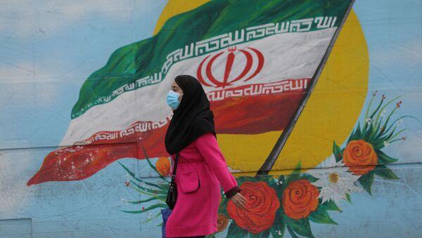 Tahran'da İran bayraklı duvar resminin önünden geçen maskeli kadın - Sputnik Türkiye