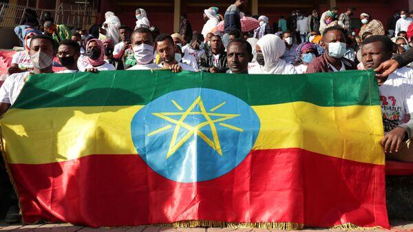 Tigray bölgesinde savaşan Etiyopya federal ordusunun yaralı askerlerine kan bağışı için Addis Ababa'daki stadyumda sıraya giren binlerce kişi, Etiyopya bayrağı tutarken  - Sputnik Türkiye