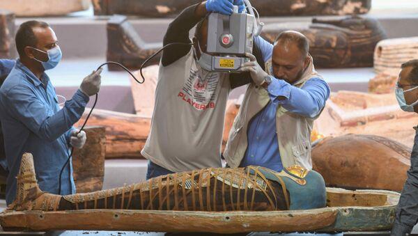 Mısır'ın  en eski antik başkenti Memphis'in Sakkara nekropolünde bulunan 2500 yıldan daha eski 100'den fazla lahitten çıkan mumyayı röntgen cihazıyla inceleyen arkeologlar - Sputnik Türkiye