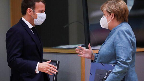 Fransa Cumhurbaşkanı Emmanuel Macron ile Almanya Başbakanı Angela Merkel, 15 Ekim 2020'deki AB zirvesinde tokalaşırken - Sputnik Türkiye