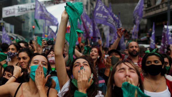 Arjantinli kadın hakları savunucuları, kürtaj yanlılarının simgesi yeşil eşarplar eşliğinde Kongre önünde kamp kurup gövde gösterisi yaptı. Serbest ve Güvenli Yasal Kürtaj Hakkı İçin Ulusal Kampanya destekçisi binlerce kadın, Meclis'teki tartışma ve oylamayı dev ekranlardan takip edip sonucu gözyaşları içinde birbirlerine sarılarak kutladı. - Sputnik Türkiye