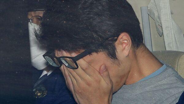 Japonya başkenti Tokyo'da polis aracında götürülürken yüzünü kapatan 'Twitter katili' Takahiro Shiraishi (Şiraişi) - Sputnik Türkiye