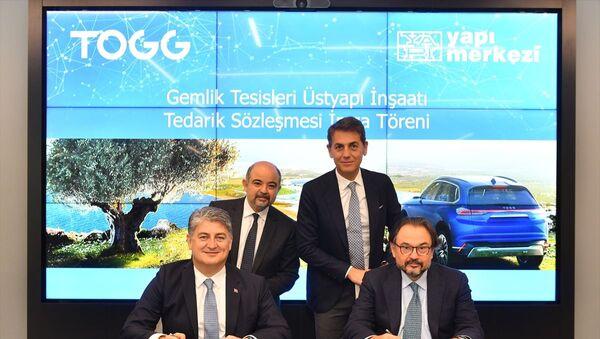 Türkiye'nin Otomobili Girişim Grubu'nun (TOGG) Bir Fabrikadan Daha Fazlası olarak tanımlanan Gemlik tesisinin üstyapı inşaatını Yapı Merkezi gerçekleştirecek. İmza törenine, TOGG Üst Yöneticisi (CEO) Gürcan Karakaş (ön solda) ile Yapı Merkezi İnşaat ve Sanayi AŞ Yönetim Kurulu Başkanı Başar Arıoğlu (ön sağda) katıldı. - Sputnik Türkiye