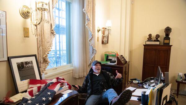 Trump destekçilerinden Richard Barnett, Temsilciler Meclisi Başkanı Nancy Pelosi'nin ofisinde oturuyor. - Sputnik Türkiye