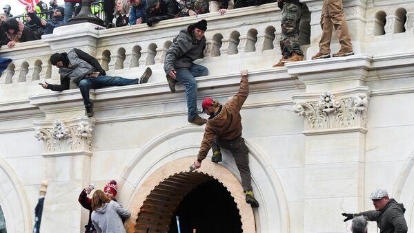 Binayı çevreleyen Trump destekçileri tırmanarak balkon üzerinden ana girişe ulaştı. - Sputnik Türkiye