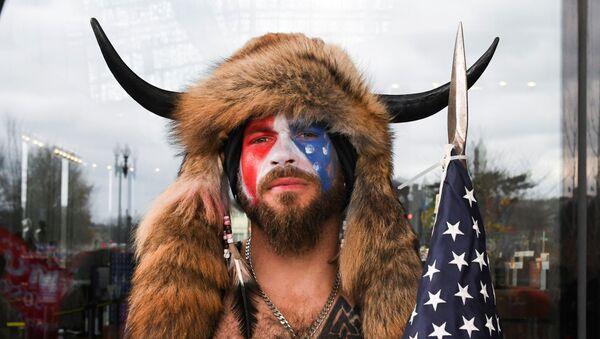 ABD Kongresi'ne saldıran Donald Trump yandaşları arasından üstü çıplak, yüzü ABD bayrağına boyanmış halde kürklü-boynuzlu şapkasıyla öne çıkanJake Angeli, namı diğer 'QAnon şamanı' - Sputnik Türkiye
