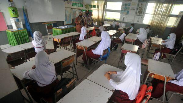 Endonezya'nın Batı Sumatra eyaletindeki Padang şehrinde bir okulda ders görülürken tesettürlü öğretmen ve öğrenciler - Sputnik Türkiye