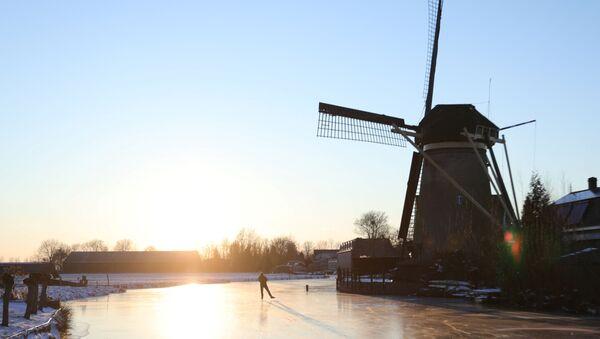 Değirmenleriyle meşhur Hollanda'nın Molenaarsgraaf bölgesinde kışın tutan buzlarda paten yapan bir erkek - Sputnik Türkiye