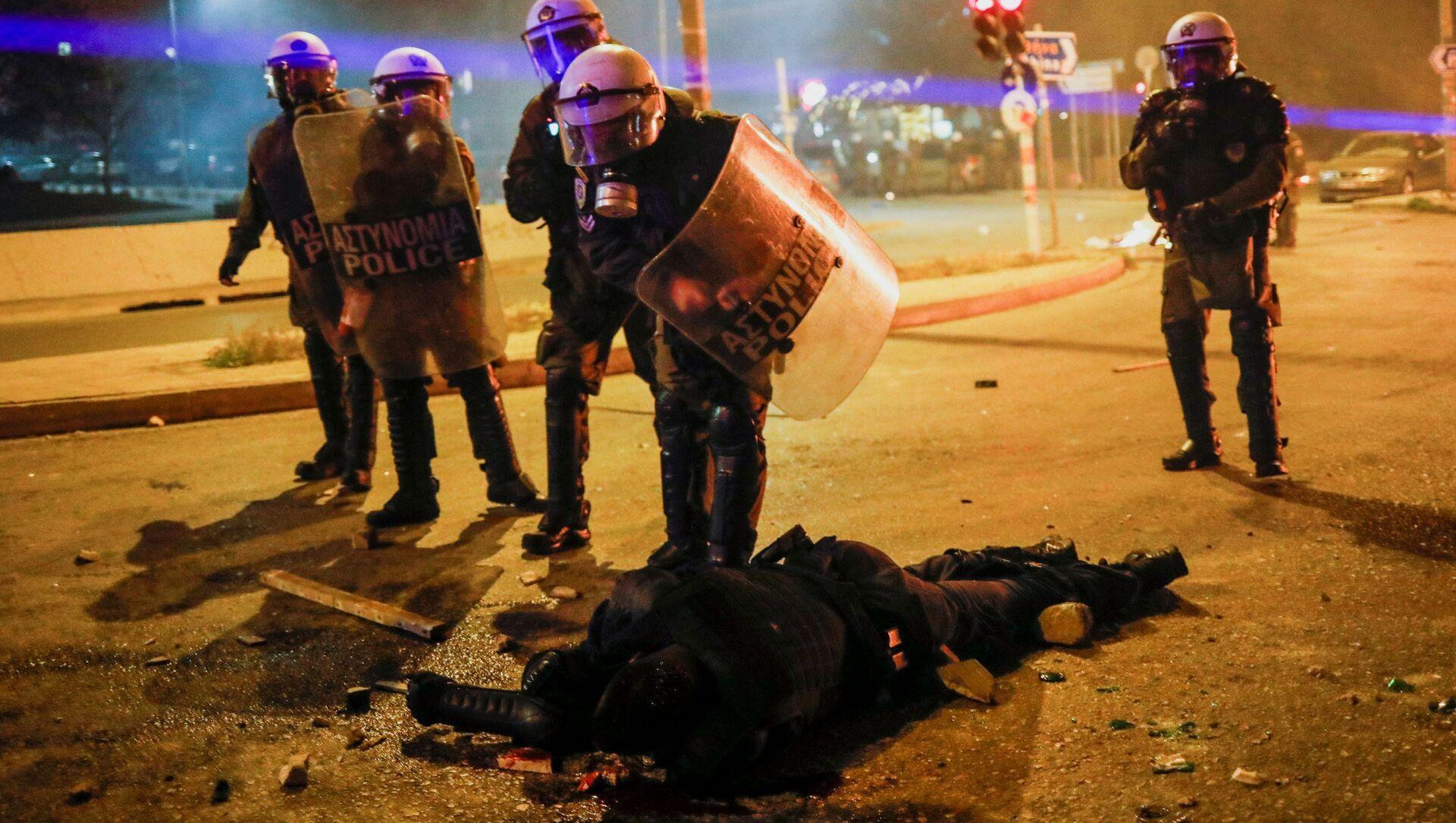 Atina'da çatışmaya dönüşen protestoda Yunan polis memurları dövülüp kanlar içinde yerde kalan arkadaşlarını hastaneye kaldırdı. - Sputnik Türkiye, 1920, 10.03.2021