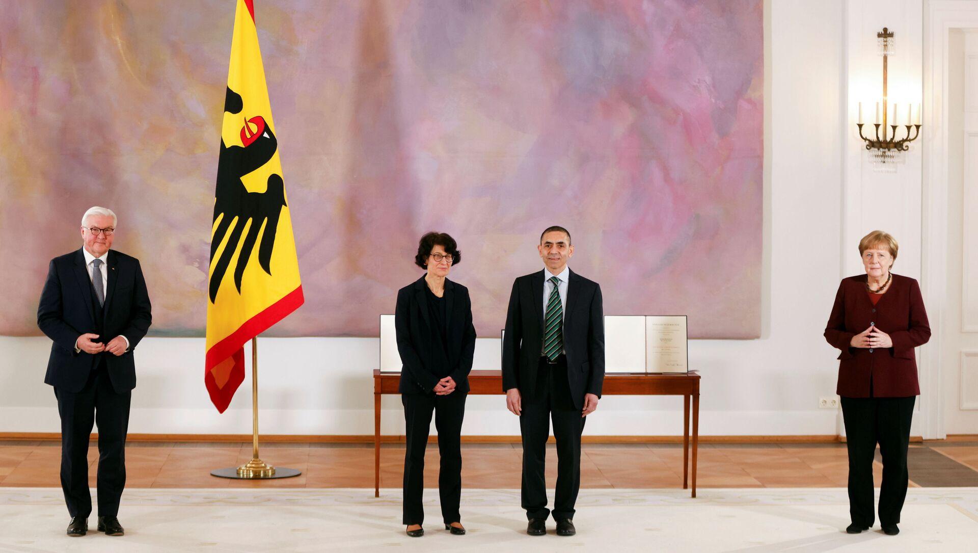 CumhurbaşkanıFrank-Walter Steinmeier'in Bellevue Sarayı'nda düzenlediği veBaşbakan Angela Merkel'in de katıldığıtörende,BioNTech'i kurup yönetenTürkiye kökenli Özlem Türeci-Uğur Şahin çiftine,Almanya'nın en üst düzey devlet madalyası olan Liyakat Nişanı takdim edildi. - Sputnik Türkiye, 1920, 19.03.2021