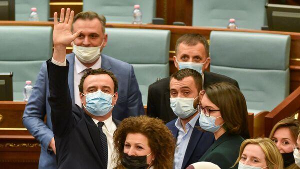 Kosova meclisinde yeniden başbakan seçilen Albin Kurti yemin ettikten sonra el sallarken - Sputnik Türkiye