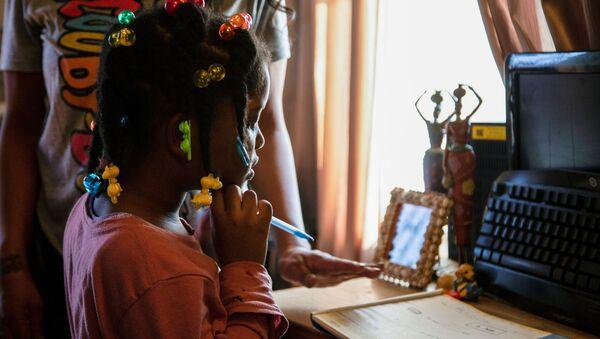 ABD'nin Kentucky eyaletinin Louisville kentinde uzaktan eğitim alan çocuk ile ona yardım eden velisi - Sputnik Türkiye