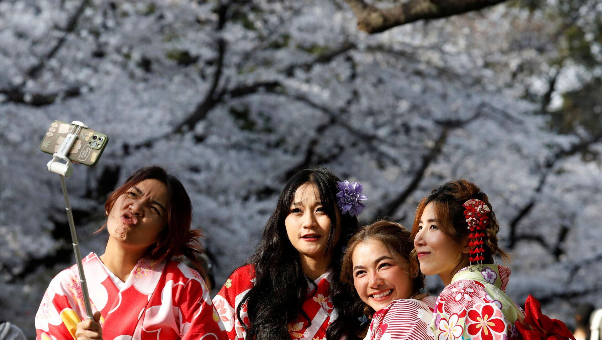 Japon başkenti Tokyo'nun Ueno Parkı'nda kiraz ağaçlarının çiçek (sakura) açmasını selfie çekerek kutlayan kimono giymiş kadınlar - Sputnik Türkiye, 1920, 01.04.2021
