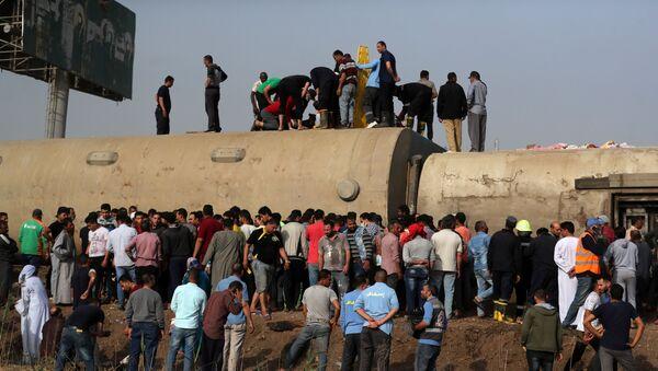 Mısır'da bu kez Kalyubiye vilayetinde bir yolcu treni raydan çıkarak devrildi. Olay yerinde toplananlar devrilen vagonların üzerine çıktı. - Sputnik Türkiye