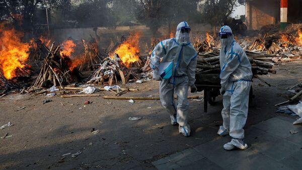 Hindistan başkenti Yeni Delhi'de Kovid-19 kurbanlarının yakıldığı krematoryuma odun taşıyan koruma kıyafetli sağlık çalışanları - Sputnik Türkiye