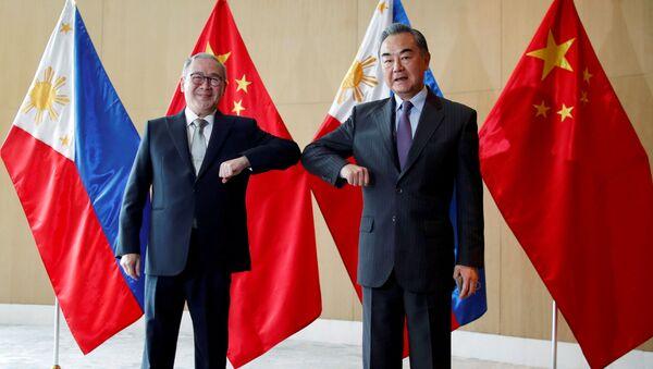 Filipinler Dışişleri Bakanı Teodoro Locsin ile Çin Dışişleri Bakanı Wang Yi, Manila'daki görüşmede dirsek selamı verirken - Sputnik Türkiye