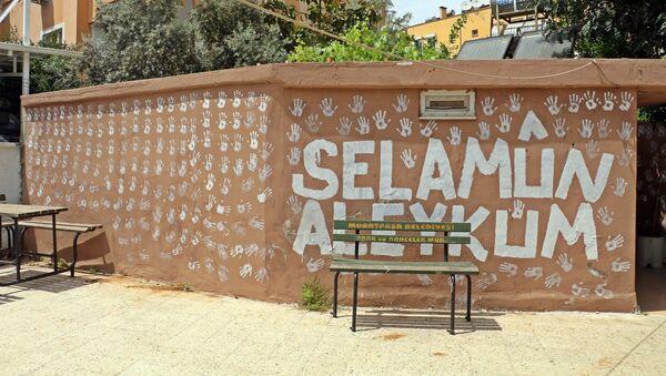 """Antalya'da bir genç, boya kovasına batırdığı ellerinin iziyle caminin bahçe duvarlarına 'selamlama' motifleri yaptı. İmam gençten şikayetçi olurken genç ise, """"Kimse birbirine selam vermiyordu"""" diyerek kendini savundu. - Sputnik Türkiye"""