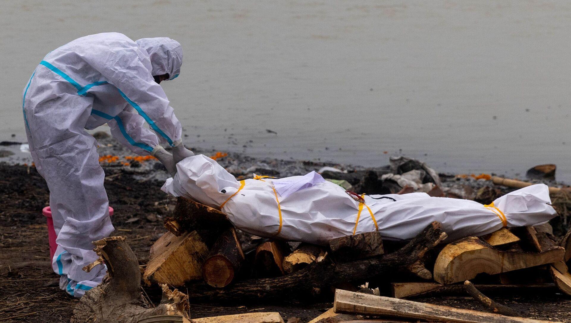 Kovid-19'dan ölen yakınıyla Ganj Nehri kıyısında yakılmasından önce koruyucu kıyafetler giyerek vedalaşan Hindistanlı (Uttar Pradeş, Garhmukteshwar) - Sputnik Türkiye, 1920, 11.05.2021