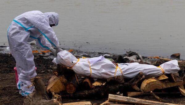 Kovid-19'dan ölen yakınıyla Ganj Nehri kıyısında yakılmasından önce koruyucu kıyafetler giyerek vedalaşan Hindistanlı (Uttar Pradeş, Garhmukteshwar) - Sputnik Türkiye