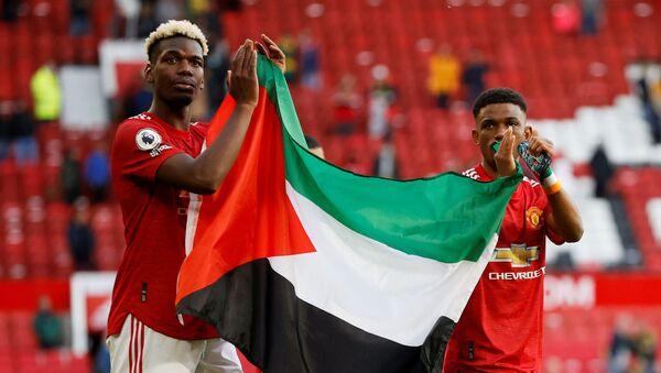 İngiltere Premier Lig ekibi Manchester United oyuncuları Paul Pogba ve Amad Diallo, Fulham maçının ardından Filistin bayrağı açtı. - Sputnik Türkiye