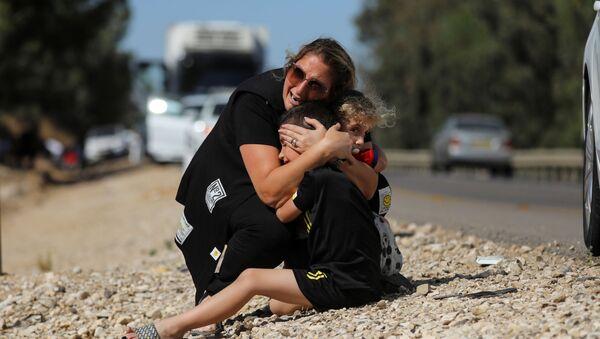 Gazze'den atılan roketler nedeniyle sirenlerin çaldığı İsrail'in Siderot kentinde çocuklarını korumaya çalışan kadın - Sputnik Türkiye