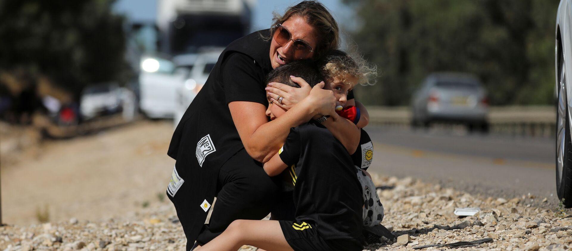 Gazze'den atılan roketler nedeniyle sirenlerin çaldığı İsrail'in Siderot kentinde çocuklarını korumaya çalışan kadın - Sputnik Türkiye, 1920, 19.05.2021