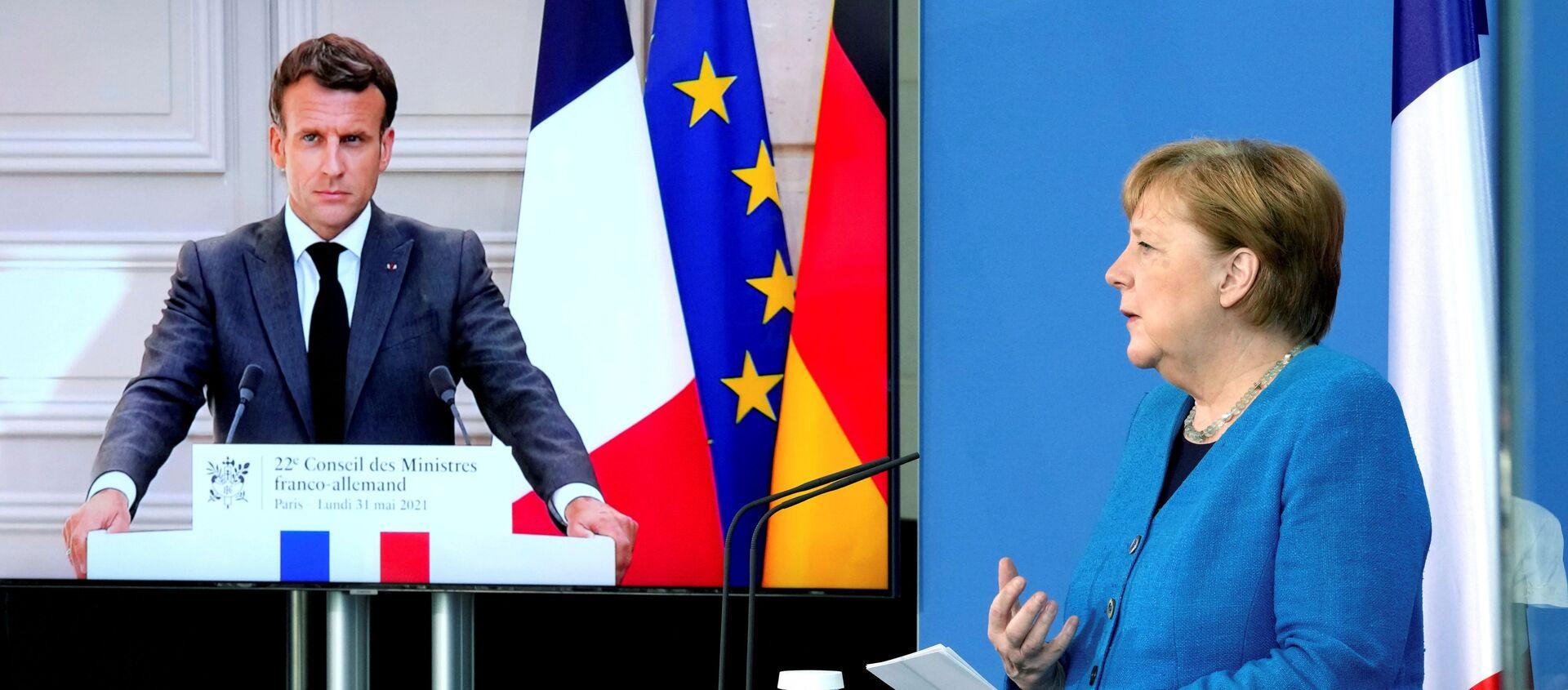 Emmanuel Macron ile Angela Merkel video konferansla gerçekleşen Fransa-Almanya Bakanlar Konseyi toplantısı sırasında  - Sputnik Türkiye, 1920, 31.05.2021
