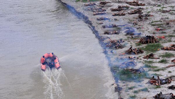 Hindistan'da şiddetli yağışın ardından Ganj Nehri yükseldi. Nehrin geri çekilmesinin ardından sahile gömülen koronavirüs kurbanlarının cesetleri yüzeye çıktı. - Sputnik Türkiye