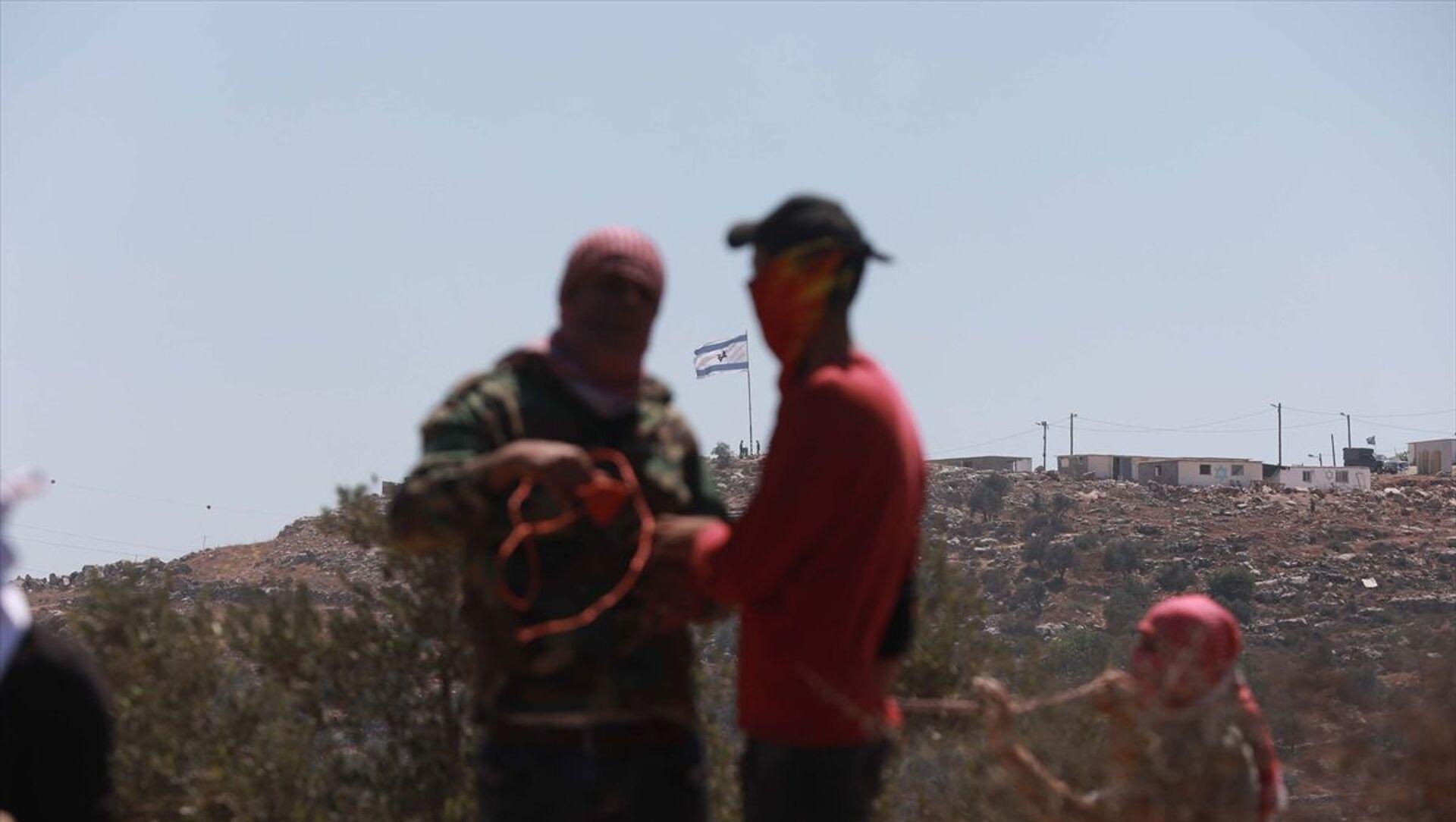 Batı Şeria'nın Nablus kentine bağlı Beyta beldesinde toplanan bir grup Filistinli, yasa dışı Yahudi yerleşim birimleri karşıtı gösteri düzenledi. İsrail güçlerinin göstericilere müdahale etmesi üzerine Filistinliler, bölgede taş atarak karşılık verdi. - Sputnik Türkiye, 1920, 02.07.2021