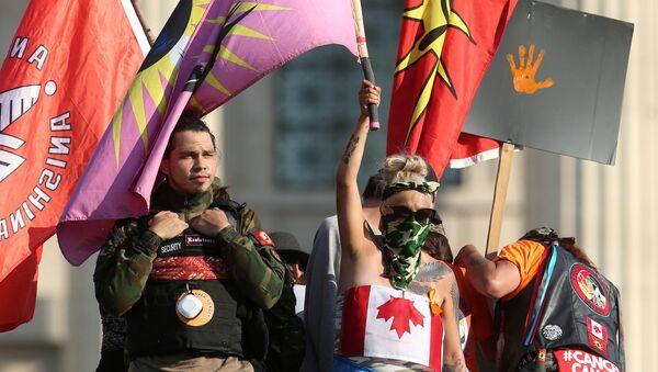 1 Temmuz Kanada Günü'nün yerli çocuk mezarlarının gölgesindekutlanmasında ısrar edilince, Winnipeg kentindeki Manitoba eyaleti parlamento binası önünde Kraliçe Victoria heykelini yıkıp kaidesine çıkan protestocular - Sputnik Türkiye