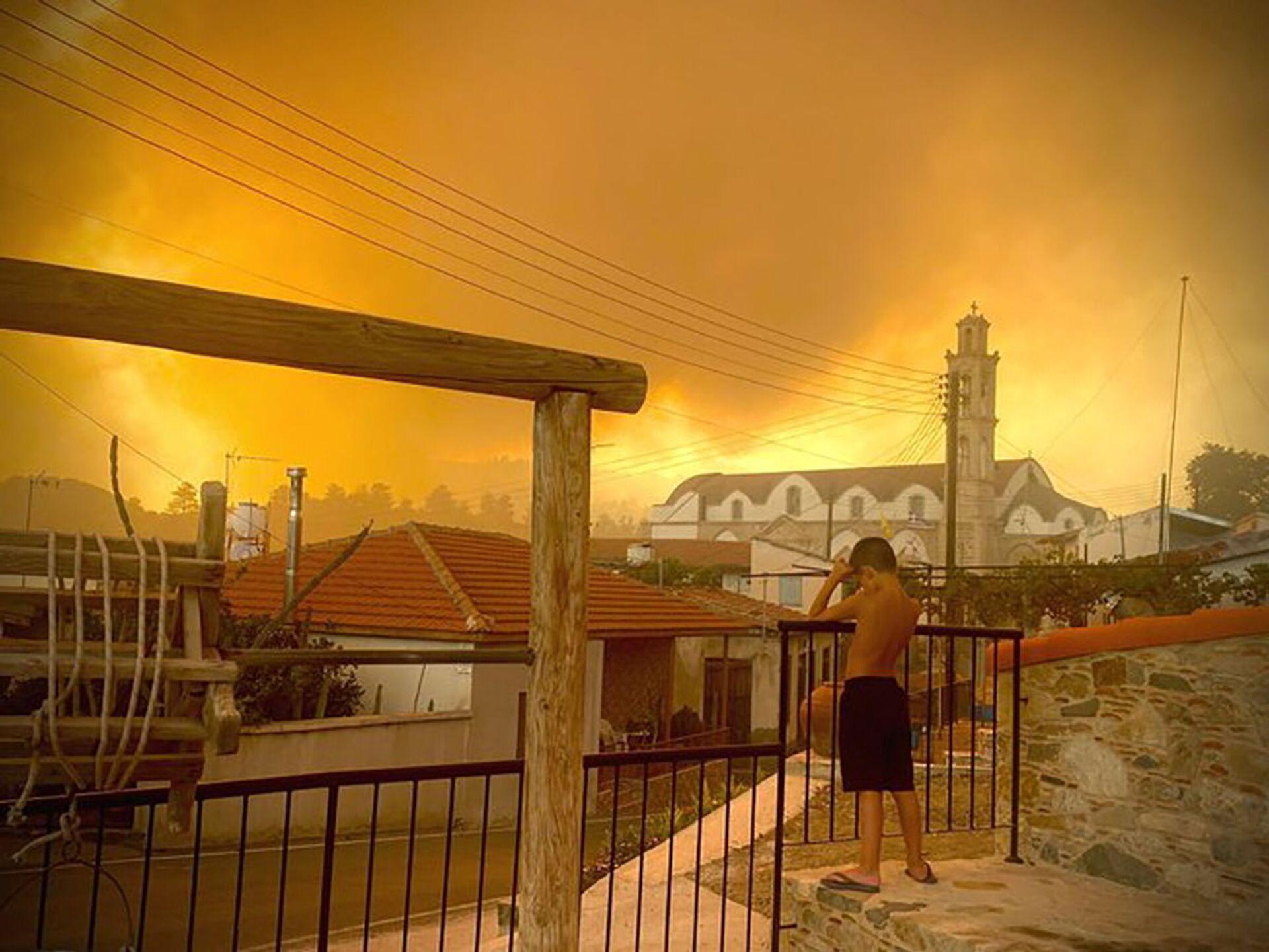 Larnaka yakınındaki Ora köyünde bir erkek çocuğu, yaklaşan orman yangınını endişeyle izledi. Elektrik hatlarının yanması sonucu bölgede kesintiler de yaşandı. - Sputnik Türkiye, 1920, 10.08.2021