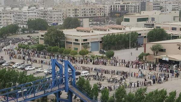 Pakistan'ın Karaçi kentinde Koronavirüs (Kovid-19) aşısı olmak isteyen vatandaşlar, Karaçi Fuar Merkezi'nde kurulan Kovid-19 aşı merkezinde yüzlerce metrelik aşı kuyruğu oluşturdu. - Sputnik Türkiye