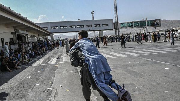 Волонтер с раненым афганцем в аэропорту Кабула  - Sputnik Türkiye