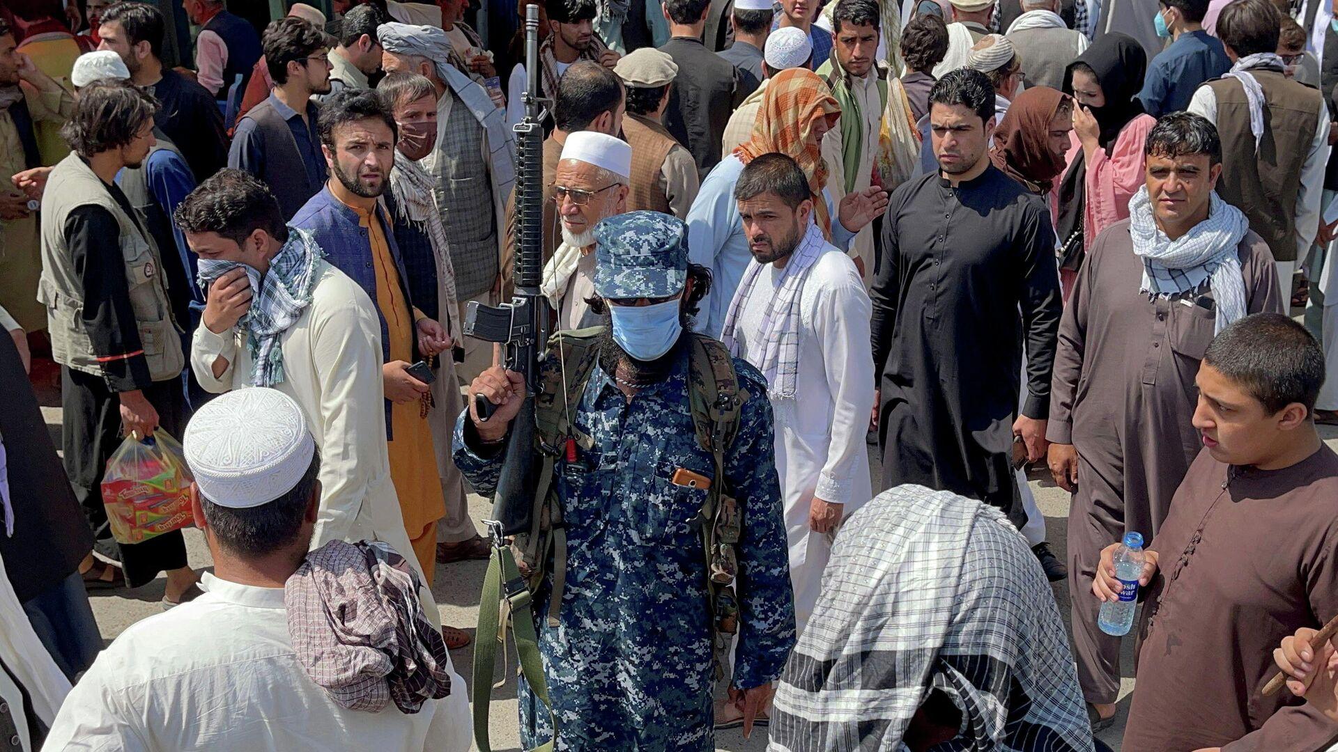 Afganistan başkenti Kabil'de sokaktaki kalabalık arasında devriye gezen silahlı Taliban militanı - Sputnik Türkiye, 1920, 24.09.2021
