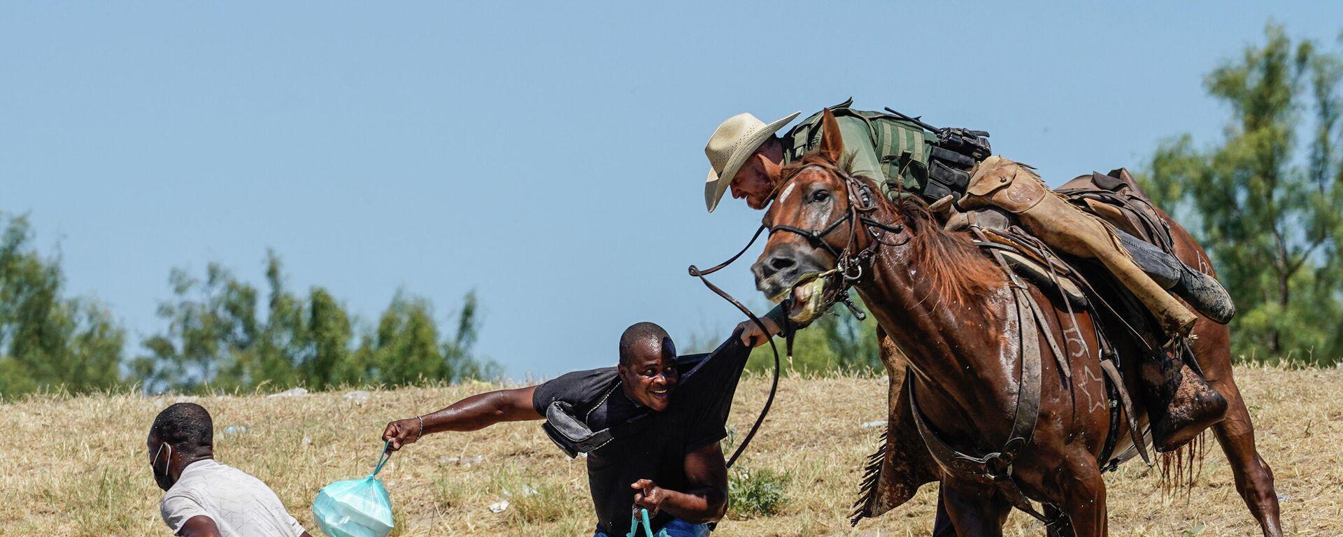 Teksas eyaletinde ABD Sınır Devriyesi'ne (USBP) bağlı federal polis memurları, at üzerinde dizginlerle Haiti göçmenleri yakalayıp Rio Grande Nehri'ne sürerken  - Sputnik Türkiye, 1920, 21.09.2021