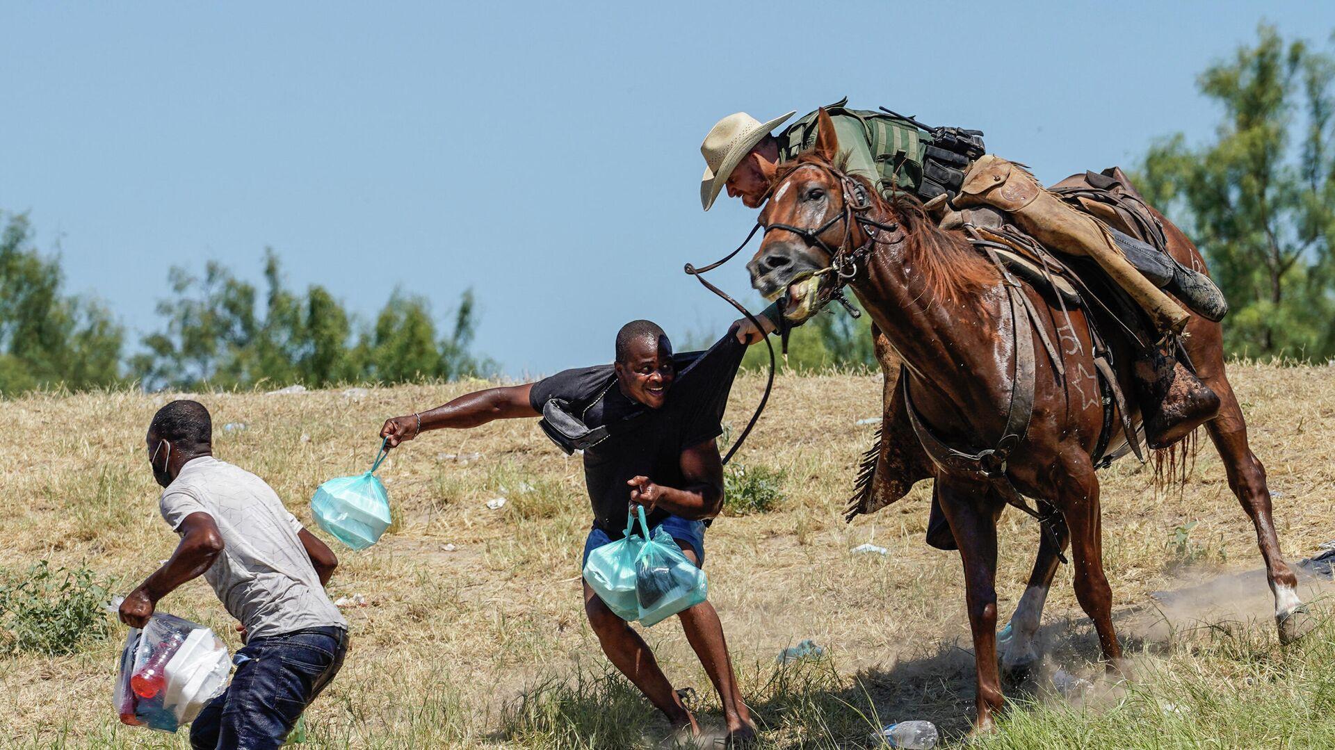 Teksas eyaletinde ABD Sınır Devriyesi'ne (USBP) bağlı federal polis memurları, at üzerinde dizginlerle Haiti göçmenleri yakalayıp Rio Grande Nehri'ne sürerken  - Sputnik Türkiye, 1920, 23.09.2021