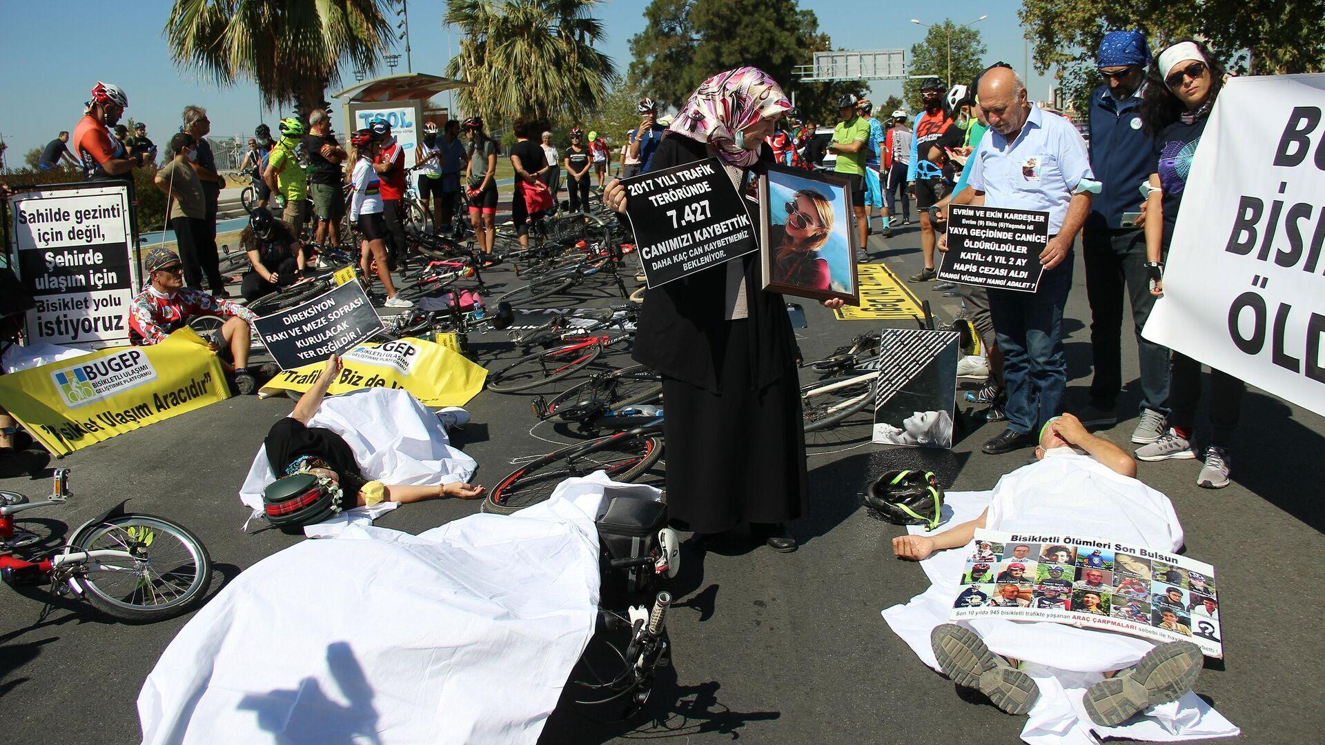 Türkiye'de son iki yılda 285 bisikletlinin trafik kazalarında hayatını kaybetmesi üzerine toplanan İzmirli bisikletçiler, kefen giyip eylem gerçekleştirdi. Eylemde geçen yıl hayatını kaybeden bisiklet sporcusu Zeynep Aslan'ın ailesi de yer aldı. - Sputnik Türkiye, 1920, 26.09.2021