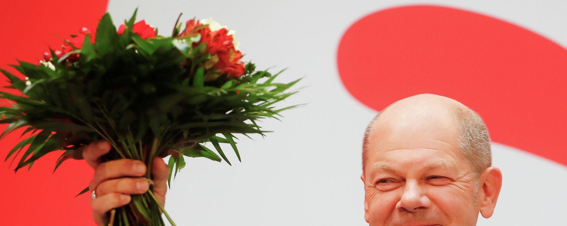 Almanya'da genel seçim ertesi Sosyal Demokrat Parti (SPD) merkezinde düzenlenen kutlamada başbakan adayı Olaf Scholz elinde çiçek buketiyle - Sputnik Türkiye, 1920, 27.09.2021