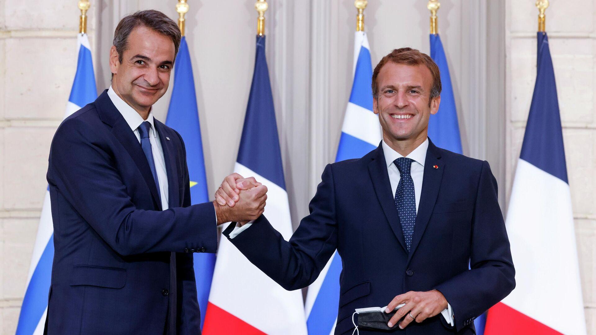 Paris'i ziyaret eden Yunanistan Başbakanı Kiriakos Miçotakis, silah ve savunma anlaşmaları yaptığı Fransa Cumhurbaşkanı  Emmanuel Macron ile el sıkışırken (28 Eylül 2021) - Sputnik Türkiye, 1920, 28.09.2021