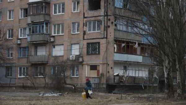 Bir kadın, Avdeyevka kentinde çatışmalar nedeniyle yıkılan çok katlı apartman binasının önünden geçiyor - Sputnik Türkiye