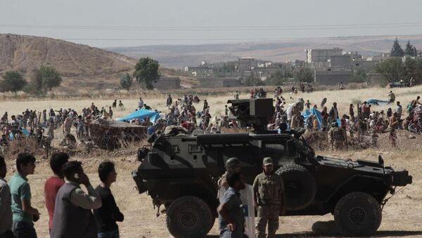 Halep'e bağlı Kobani kentinde (Ayn el Arap), DAEŞ ile bazı Kürt gruplar arasındaki çatışmalardan kaçan bir grup Suriyeli sınırda bekliyor. - Sputnik Türkiye