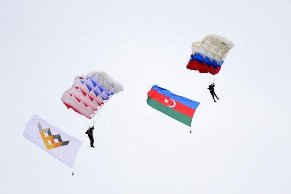 Uluslararası Ordu oyunlarının resmi açılış töreninde katılımcı ülkelerin bayraklarını taşıyan paraşütlü birlikle alana indi - Sputnik Türkiye