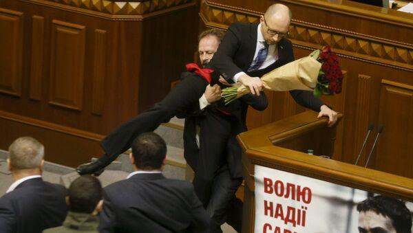 Ukrayna'da iktidardaki Poroşenko Cephesi Partisi'nden milletvekili Oleg Barna, Başbakan Arseniy Yatsenyuk'u 'kucaklayarak' kürsüden indirdi. - Sputnik Türkiye